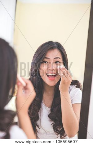 Woman Applying Make Up Into Her Face