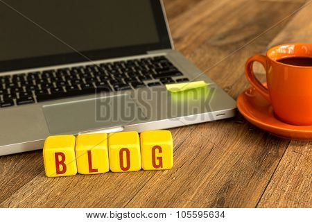 Blog written on a wooden cube in front of a laptop