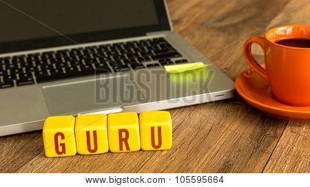 Guru written on a wooden cube in front of a laptop