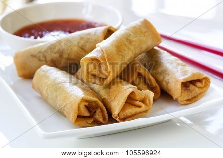 Spring rolls with chili sauce and chopsticks.