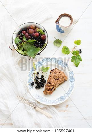 Black-currant scone bisquit with bowl of fresh garden berries and cream, top view.