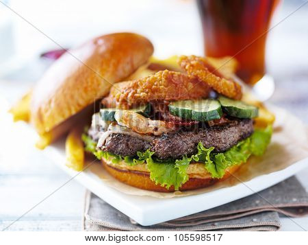 bacon barbecue burger topped with onion rings on white table served with fries served open faced