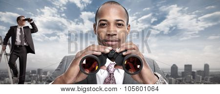 African-American businessman with binoculars over urban background.