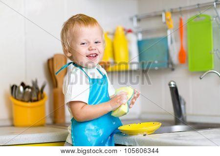 child boy washing dishes in kitchen
