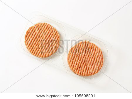 package of raw burger patties on white background