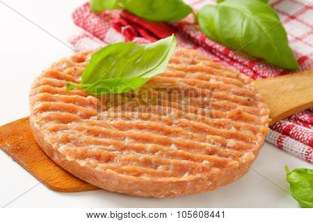 detail of raw burger patty on wooden spatula