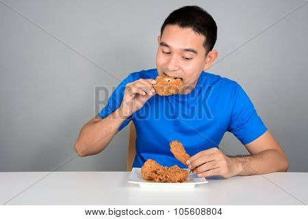 Young Man Biting Fried Chicken
