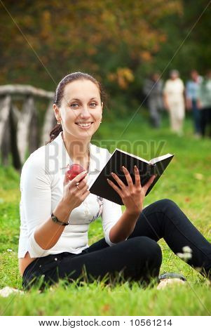 smiling woman with book and apple