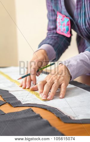 Dressmaker measuring tailor pattern on the table
