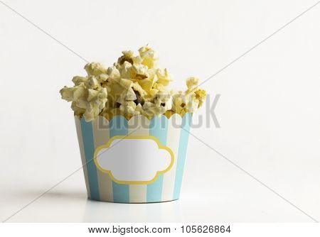 Isolated tiny paper bucket filled with hot pop corns with blank seal for the text on it.
