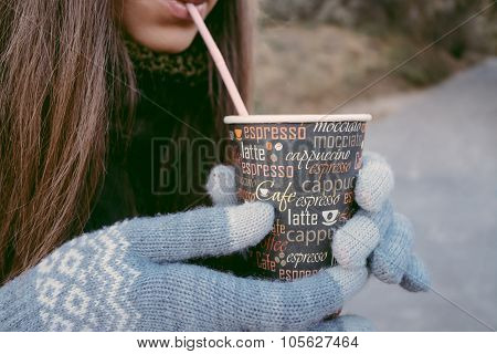 Young Woman Drinking Coffee From Disposable Cup While Walking