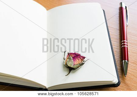 Open Notebook With Dry Rose On Wooden Table With Copy Space