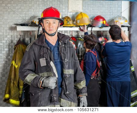 Portrait of confident mature fireman at fire station with team in background