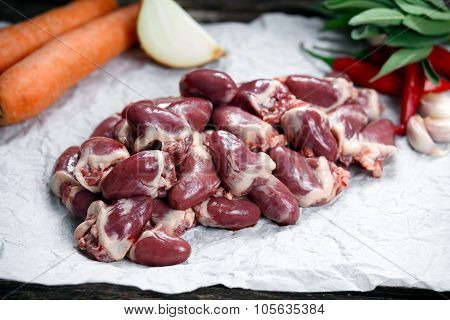 Raw Duck Hearts On Crumpled Paper, Decorated With Vegetables. On
