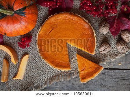Sliced homemade pumpkin tart pie sweet dessert food with nuts and autumn composition on vintage wood