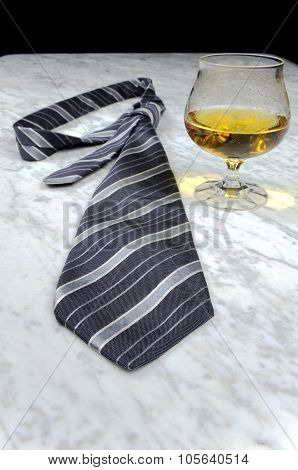 Striped Tie With A Glass Of Brandy On The Marble Table