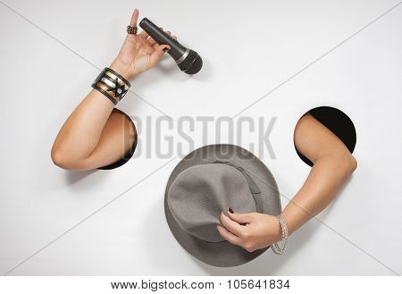 Female hands with microphone and hat