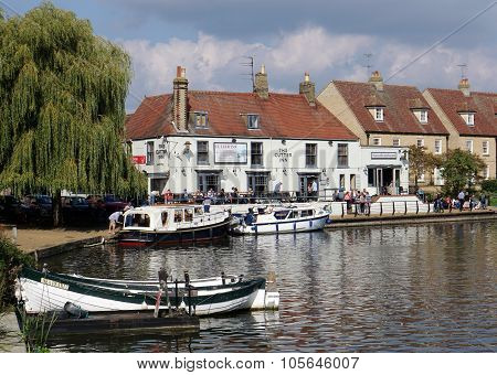 ELY, UK - SEPTEMBER 20 2015: People walk alongside the River Great Ouse and eat on the patio of a riverside pub in the small tourist town of Ely, Cambridgeshire.