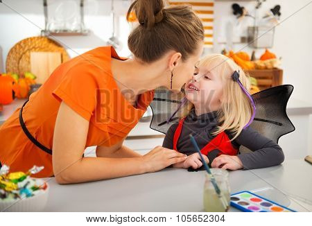 Mother With Halloween Dressed Daughter In Decorated Kitchen