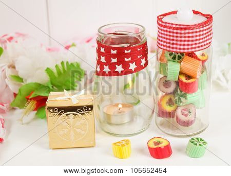 Traditional fruity boiled sweets, a candle and a gift