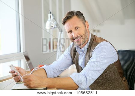 Handsome man sitting in office using smartphone