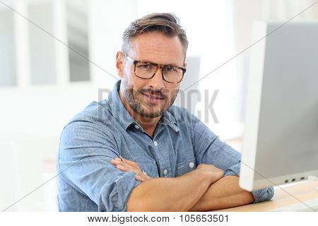Handsome man with eyeglasses sitting in front of desktop