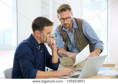 Businessmen in office working on project