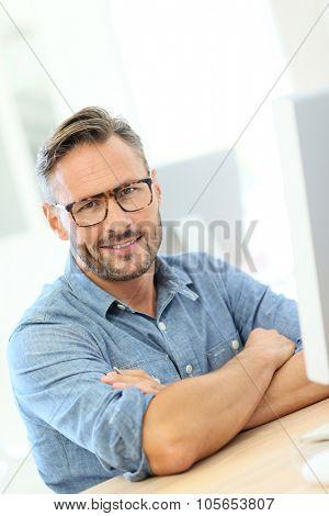 Handsome man with eyeglasses sitting in front of desktop