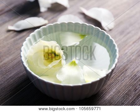 Flower petals in bowl with water on wooden background