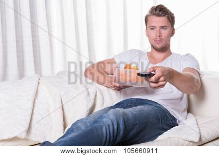 Portrait Young Man Sitting On Couch And Eating Chips And Zapping TV