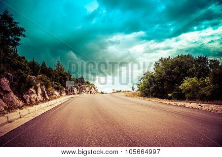 Long Endless Road In Countryside With No Traffic With Dramatic Clouds