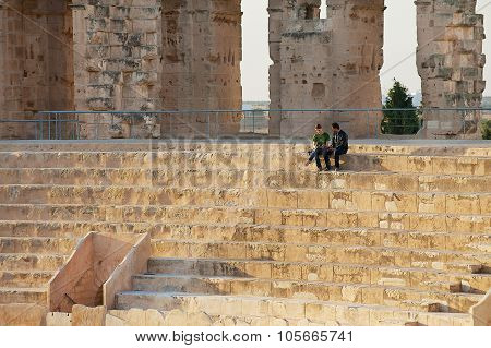 People sit at the stairs of the El Djem amphitheater in El Djem, Tunisia.