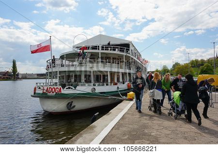 SZCZECIN POLAND - MAY 02 2015: Group of people close by a tourist boat on the Odra river