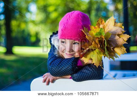 Cute Daydreaming Girl Sitting On The Bench With Maple Leaves In Park