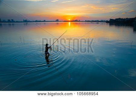 Fisherman in sunset in West Lake, Hanoi, Vietnam