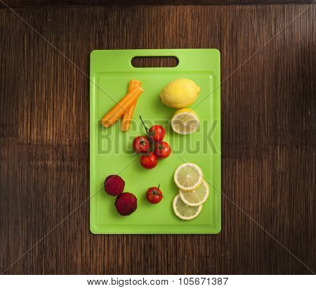 lemon , mini tomatoes carrot and beetroot on green plastic cutting surface on wooden background