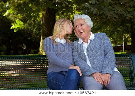 Woman Whispering To Senior Woman