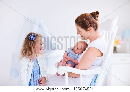 Mother With Daughter And Baby In A White Nursery