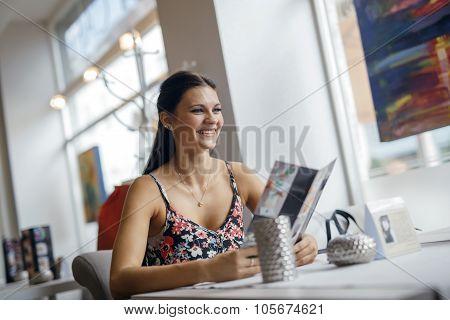 Pretty Women Looking At Menu In Restaurant