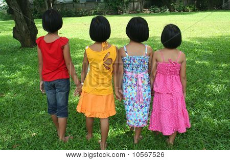 Four girls walk in the park.