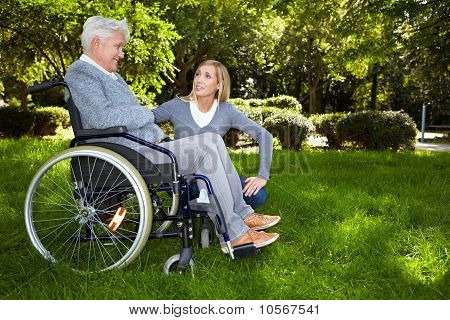 Nurse Talking To Woman In Wheelchair In Park