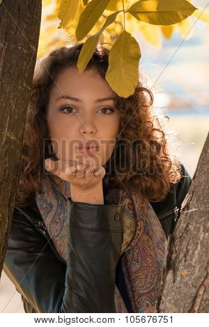 Beautiful young girl sending kisses between two branches and yellow leaves - outdoors autumn portrait