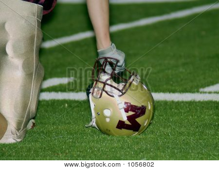 Football Player Leaning On Helmet
