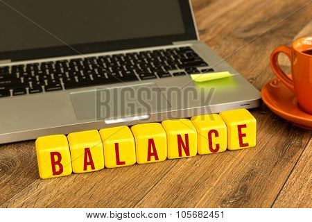 Balance written on a wooden cube in front of a laptop