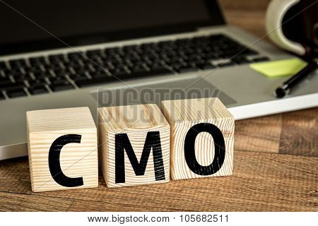 CMO (Chief Marketing Officer) written on a wooden cube in front of a laptop