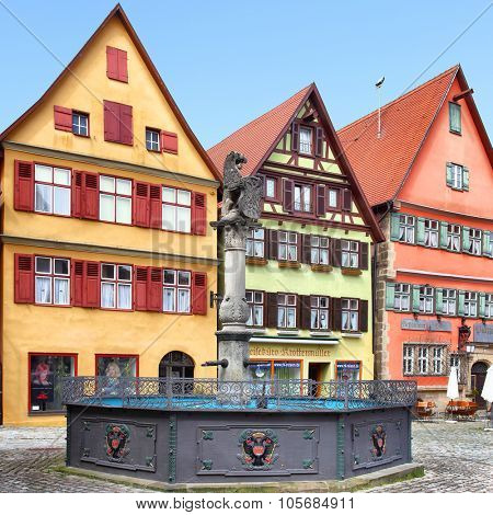 DINKELSBUHL, GERMANY - April 26, 2013: Colorful medieval houses with small shops and fountain on old square in Dinkelsbuhl
