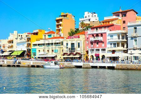 AGIOS NIKOLAOS, GREECE - JUNE 30, 2015: Picturesque waterfront with colorful houses, taverns, shops and boats in harbor in Agios Nikolaos, Crete Island