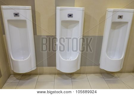 Closeup of three white urinals in men's bathroom.