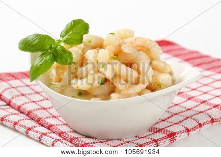 close up of pan fried shrimps in white bowl on checkered dishtowel
