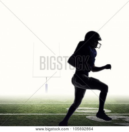 Silhouette American football player runing against american football posts